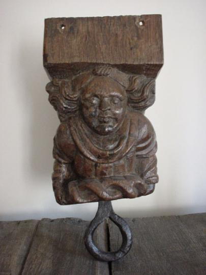 Humourous medieval oak font cover pulley of an angel lifting a crown of thorns